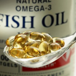 Fish oil softgels in a spoon, bottle with capsules on the background